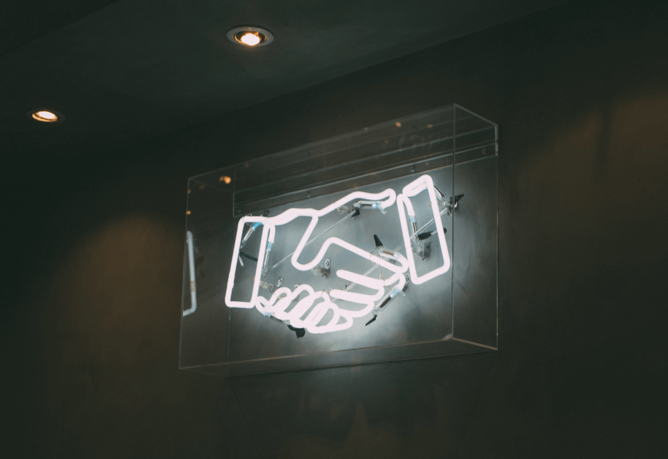 A lit up sign of a handshake